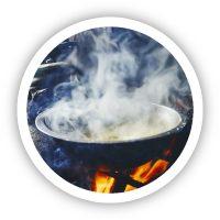 Lady heating PapStix on a fire stove